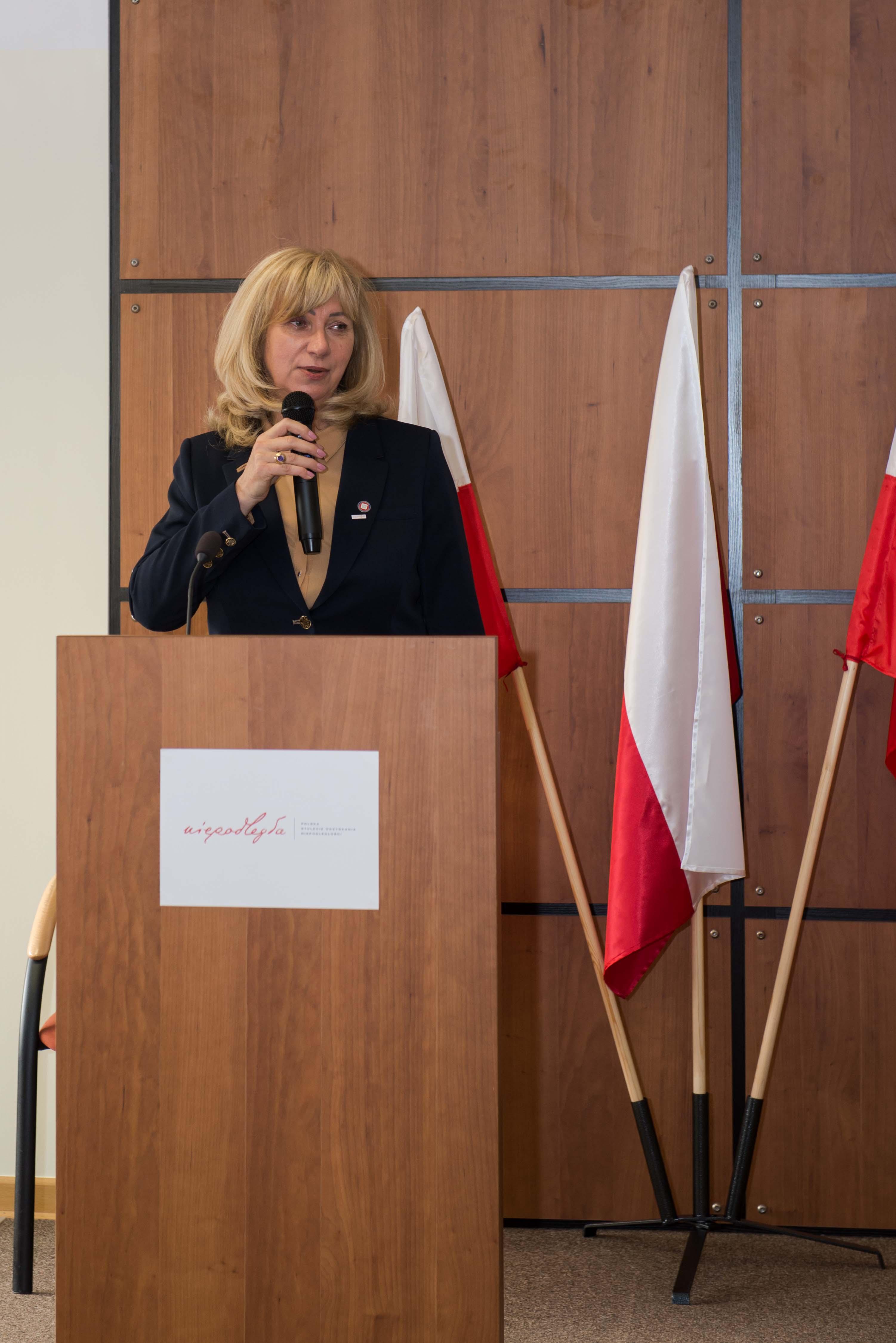Konferencja jubileuszowa z okazji 100-lecia odzyskania niepodległości i 99-lecia służb sanitarnych w Polsce. Na mównicy stoi pani Maria Pawlak, Państwowy Wojewódzki Inspektor Sanitarny w Warszawie. Otwarcie konferencji i przywitanie zaproszonych gości.
